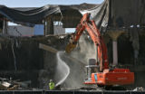 Water is sprayed to keep down the dust, as a demolition excavator works on taking down the...