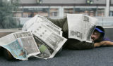 A young woman makes a blanket out of newspaper and catches some sleep on the main terminal at...