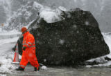 MJM601 CDOT worker, Greg Fox (cq) walks past a 50 ton boulder that blocked 285 South outside of...