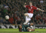MDT124 - Manchester United's Wayne Rooney, right, beats AC Milan's Dida, left, to score a goal...
