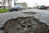 DLM3751  Vehicles pass by two large potholes in the middle of W. 13th Avenue just east of Osage...