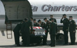 members of the Honor Guard unload the casket of Army Cpl. Wade Oglesby from the plane at Walker...