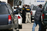 Department of Justice, Metro Gang Task Force and local law enforcement gather around an Aurora...