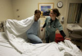 Temequa Edwards (cq), 21, crawls back into bed with help from nurse Kelly Fox (cq) Wednesday,...