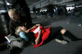 Arriving passengers shuffle towards baggage claim as Shelly Remien (cq) catches some sleep on the...