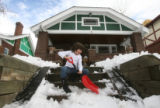 Mathilda Bates, 6, clears snow from the steps of her house in the 800 block of Gilpin Street in...