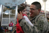 (DLM2287) -   Army Sgt. Jose Torres of Englewood holds his six-month-old daughter Carmen for the...