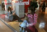 MJM046 Claire Casey, 7, of Littleton holds her doll in the window of Crate & Barrel as she...