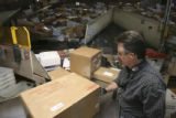 John Bove, package distribution clerk, manually enters either the zip code or the bar code...