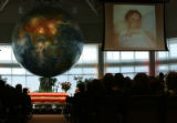 MJM137 Photos of PFC Seth M. Stanton play on a large screen as people continue to file into a...