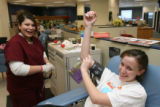 Heather Pacheco, (cq), phlebotomist, left in purple, administers the process for Julianne Reed,...