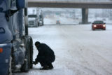 Trucker Julio Pacheco, cq, from California puts chains on his semi-truck Friday Dec.29, 2006 on...