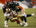 Hamza Abdullah and Patrick Chukwurah tackle Vernon Davis in the fourth quarter of the Denver...