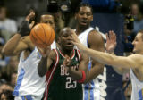 Former Denver Nugget Ruben Patterson looks to pass to his Milwaukee Bucks teammates being defended...
