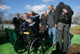 Debra Anderson (cq) gives a hug to Sgt. Gregory Edwards (cq) (in wheelchair) at the burial service...
