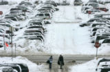 Travelers make their way through DIA parking lots and snow covered cars Friday morning Dec. 29,...