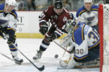 BG0044 Colorado Avalanches' Pierre Turgeon, center, attacks St. Louis Blues' goalie Jason...