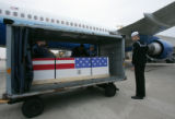 Navy Hospital Corpsman John Dragneff (cq) looks at the box containing the casket of his friend...