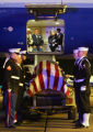 A combination Marine and Navy Honor Guard stand at attention before the casket of Navy Hospital...