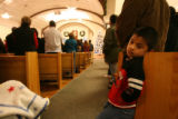 (DLM6724) -   A young boy leans on a pew as people at Our Lady of Peace Catholic Church in...