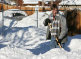 Denver Mayor Hickenlooper helps clear snow from a driveway in the 800 block of Galapago St. Sunday...