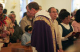 A very exhausted Fr. Bernie Schmitz (cq) walks down the aisle after the 11:30 mass at Our Lady of...