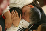 (DLM4892) -   Maria Rivas holds her two-year-old son Oscar and cries for her husband Jose Rivas...