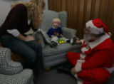 Caryn talks with her son Drew Keenan,2, (cq both from mom), as Santa takes the floor discussing...