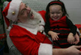 Santa shares a guffaw with Miranda Soto,2, (cq from mom) as she got adjusted and calmed down she...