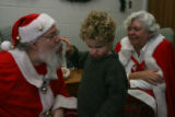 Anton Kiwimagi,3, (cq), finds Santa's nose as Mrs. Claus looks on. He was a little timid at first...