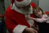 Skyla Walsh, 2-11/12th's, (cq), becomes intrigued with the holiday noises of the bells on Santa's...