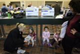 (DLM7491) -   Mindy Hartley, left, reads to her daughter, Georgia Hartley, 3, as Vivian Kenney, 2,...