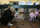 (DLM7492) -   Mindy Hartley, left, reads to her daughter, Georgia Hartley, 3, as Vivian Kenney, 2,...