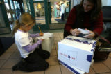 (DLM7568) -   Emily Olivier, 7, finishes writing her letter to Santa Claus as she waits in line...