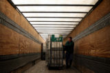 (DLM7649) -   United States Postal Service truck driver Phil Sterling unloads carts filled with...