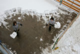 Jenna Mrnak (cq), left, and her sister Jeri Dohrmann (cq) shovel snow from the show pen they will...