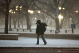 A pedestrian walks along Colfax Avenue in front of Civic Center Park during the early morning...