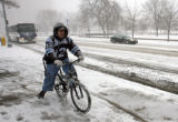 Jason Prince (cq) rides on the sidewalk at Broadway and 14th Avenue during the  morning snowfall...