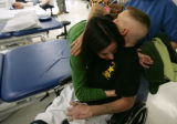 Sgt. Gregory Edwards, of the Marines, gets a hug from physical therapist Kyla Dunlavey (cq), left...