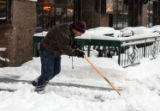 Mike Huber (cq) clears snow from in front of the Kittredge Building on the 16th Street Mall...