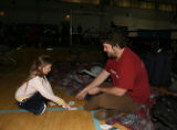 Lydia Moores (cq), left, 9 years old and new friend Steve Taylor (cq) play cards in the temporary...