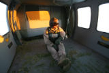 Colorado Air National Guard crew member SSGT Marc Belo, cq, sits on the floor of an unloaded UH-60...