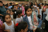 BG2998  Border Street: Laura, 9, a local child holds a statue of the Virgin Guadalupe she won in a...