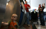 (DLM1306) -   Two-year-old Spencer Phillips plays on the floor as he waits at the ticket counter...