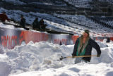 MJM086  Bill Cronan (cq) helps other day workers shovel out snow from the stands and field level...