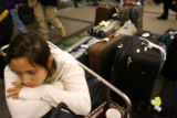 MJM337  Miranda Lieberman (cq), 13, of Coral Springs, Fla. sits surrounded by luggage as she waits...