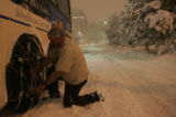 [JPM0267] RTD bus driver Richard Rainey replaces a tightener on the snow chains attached to his...
