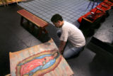 (DENVER, Colo., March 30, 2005) Chris Vigil (cq), works on a sign of the Virgen de Guadelupe,...