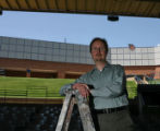 Keith Arnold, the chorale conductor at the Arvada Center, stands on a ladder in the amphitheater...