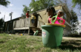 Priseila Bueno, 4, plays in a bucket of water in her yard yard Monday May 22, 2006 at the Pagel...